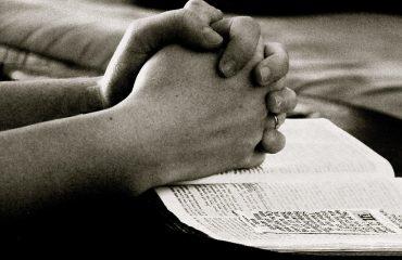 foldede hænder på bibel